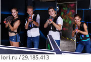Купить «girls and guys in dark laser tag room», фото № 29185413, снято 27 августа 2018 г. (c) Яков Филимонов / Фотобанк Лори
