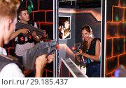 Купить «Excited people playing enthusiastically laser tag game», фото № 29185437, снято 27 августа 2018 г. (c) Яков Филимонов / Фотобанк Лори