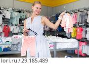 Woman 25-37 years old is choosing clothes for daughter. Стоковое фото, фотограф Яков Филимонов / Фотобанк Лори
