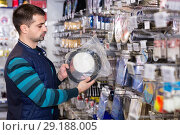 Купить «Young male choosing fishing variety accessories in the sports shop», фото № 29188005, снято 16 января 2018 г. (c) Яков Филимонов / Фотобанк Лори