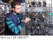 Купить «Young male choosing baitcasting reel for rod», фото № 29188017, снято 16 января 2018 г. (c) Яков Филимонов / Фотобанк Лори