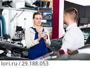 Купить «Woman mechanic with male client», фото № 29188053, снято 4 апреля 2018 г. (c) Яков Филимонов / Фотобанк Лори