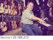 Купить «Musician male is choosing keyboard and playing on it», фото № 29188213, снято 18 сентября 2017 г. (c) Яков Филимонов / Фотобанк Лори
