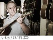 Купить «Man looking new wooden acoustic guitar in studio», фото № 29188225, снято 18 сентября 2017 г. (c) Яков Филимонов / Фотобанк Лори