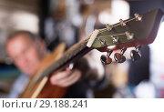 Купить «Foto of modern wooden acoustic guitar», фото № 29188241, снято 18 сентября 2017 г. (c) Яков Филимонов / Фотобанк Лори