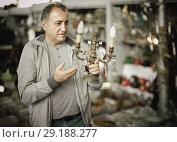 Купить «Adult male is choosing lamp at the market of old things.», фото № 29188277, снято 23 октября 2017 г. (c) Яков Филимонов / Фотобанк Лори