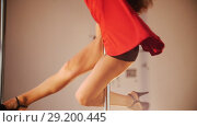 Sexy girl in red dress pole dance. Spinning around the pole. Legs shown. Стоковое видео, видеограф Константин Шишкин / Фотобанк Лори