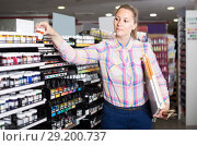 Купить «woman customer holding glass jar with color paint in art department», фото № 29200737, снято 12 апреля 2017 г. (c) Яков Филимонов / Фотобанк Лори