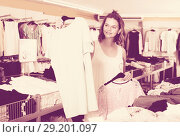 Купить «Brunette choosing new clothes in shop», фото № 29201097, снято 19 июня 2017 г. (c) Яков Филимонов / Фотобанк Лори