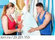 Купить «Young couple planning to surf, choosing boards and surfing suits in beach club», фото № 29201153, снято 30 апреля 2018 г. (c) Яков Филимонов / Фотобанк Лори