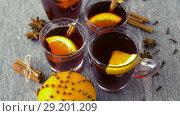 Купить «glasses of hot mulled wine with orange and spices», видеоролик № 29201209, снято 7 октября 2018 г. (c) Syda Productions / Фотобанк Лори