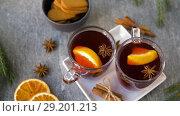 Купить «glasses of hot mulled wine with orange and spices», видеоролик № 29201213, снято 7 октября 2018 г. (c) Syda Productions / Фотобанк Лори