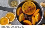Купить «pot with hot mulled wine, orange slices and spices», видеоролик № 29201249, снято 7 октября 2018 г. (c) Syda Productions / Фотобанк Лори