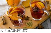 Купить «glasses of hot mulled wine with orange and spices», видеоролик № 29201577, снято 7 октября 2018 г. (c) Syda Productions / Фотобанк Лори