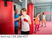 Купить «Boxing instructor and young children practicing blows», фото № 29206477, снято 12 апреля 2017 г. (c) Яков Филимонов / Фотобанк Лори