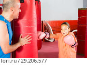 Купить «Coach holds a punching bag over which the girl beats», фото № 29206577, снято 12 апреля 2017 г. (c) Яков Филимонов / Фотобанк Лори