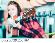 Купить «Teenage girl choosing acoustic guitar», фото № 29206861, снято 14 февраля 2017 г. (c) Яков Филимонов / Фотобанк Лори
