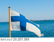 Флаг Финляндии на фоне моря и голубого неба (2018 год). Стоковое фото, фотограф E. O. / Фотобанк Лори