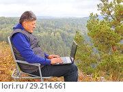 Купить «Mature male tourist is working on a laptop on top of the High Mountain.», фото № 29214661, снято 9 сентября 2017 г. (c) Акиньшин Владимир / Фотобанк Лори