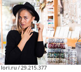 Купить «Adult woman customer in hat trying earrings», фото № 29215377, снято 16 октября 2017 г. (c) Яков Филимонов / Фотобанк Лори