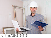 Купить «Portrait of smiling architect working at the notebook in helmet with documents», фото № 29215413, снято 18 мая 2017 г. (c) Яков Филимонов / Фотобанк Лори