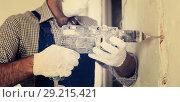 Купить «Male constructor repairing with drill in gloves», фото № 29215421, снято 18 мая 2017 г. (c) Яков Филимонов / Фотобанк Лори