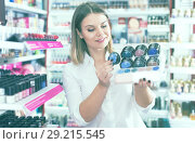 Купить «Smiling stylish girl choosing eyeshadows in shop», фото № 29215545, снято 31 января 2018 г. (c) Яков Филимонов / Фотобанк Лори