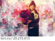 Купить «Girl buying Christmas floral compositions», фото № 29215613, снято 22 декабря 2016 г. (c) Яков Филимонов / Фотобанк Лори