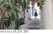 Купить «Young beautiful girl tourist, walks through old narrow street of city and takes pictures of extramural. Summer sunny day in Marmaris», видеоролик № 29231381, снято 20 октября 2018 г. (c) Сергей Тимофеев / Фотобанк Лори