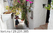Купить «Young beautiful girl tourist, walks through old narrow street of city and takes pictures of extramural. Summer sunny day in Marmaris», видеоролик № 29231385, снято 20 октября 2018 г. (c) Сергей Тимофеев / Фотобанк Лори