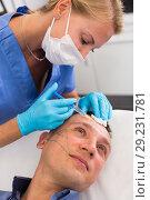 Купить «Female doctor is doing injection to patient in skin of face», фото № 29231781, снято 20 марта 2019 г. (c) Яков Филимонов / Фотобанк Лори