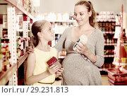 Купить «Woman with daughter are choosing fresh goods in food department», фото № 29231813, снято 5 июня 2017 г. (c) Яков Филимонов / Фотобанк Лори