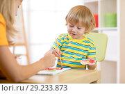 Купить «Child with teacher draw paints in play room. Preschool.», фото № 29233873, снято 12 декабря 2018 г. (c) Оксана Кузьмина / Фотобанк Лори
