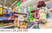 Купить «Russia, Samara, August, 2018: a woman with purchased products is at the cashier's desk in the supermarket. text in Russian: cat litter, pate», фото № 29234185, снято 20 августа 2018 г. (c) Акиньшин Владимир / Фотобанк Лори