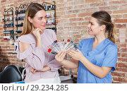 Купить «Manicure girl showing to client polish color schemes», фото № 29234285, снято 30 мая 2018 г. (c) Яков Филимонов / Фотобанк Лори