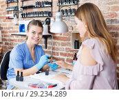 Купить «Manicurist doing procedure of manicure nail to woman client in salon», фото № 29234289, снято 30 мая 2018 г. (c) Яков Филимонов / Фотобанк Лори