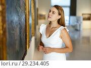 Купить «Woman visiting painting exhibition», фото № 29234405, снято 28 июля 2018 г. (c) Яков Филимонов / Фотобанк Лори
