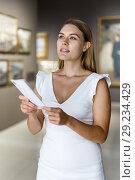 Купить «Woman visiting painting exhibition», фото № 29234429, снято 28 июля 2018 г. (c) Яков Филимонов / Фотобанк Лори