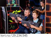 Купить «Happy teen boy with laser gun having fun on lasertag arena with his father», фото № 29234545, снято 3 сентября 2018 г. (c) Яков Филимонов / Фотобанк Лори
