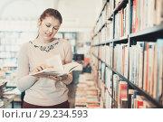 Купить «Young woman browsing inside of books while visiting public libra», фото № 29234593, снято 22 февраля 2018 г. (c) Яков Филимонов / Фотобанк Лори