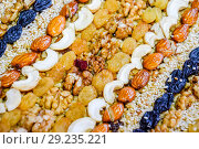 Купить «Kozinaki covered with nuts and seeds. Almonds, cashews and raisins.», фото № 29235221, снято 26 марта 2019 г. (c) Леонид Еремейчук / Фотобанк Лори