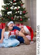 Купить «Dad and daughter under the Christmas tree», фото № 29236685, снято 14 октября 2018 г. (c) Типляшина Евгения / Фотобанк Лори