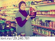 Купить «female consumer holding glass jar of tomatoes», фото № 29240781, снято 15 декабря 2017 г. (c) Яков Филимонов / Фотобанк Лори