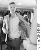Купить «Male in suit trying jacket in the clothes store», фото № 29240881, снято 28 сентября 2017 г. (c) Яков Филимонов / Фотобанк Лори