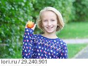 Купить «Красивая девочка блондинка на прогулке в парке ест фрукты, нектарин или персик», фото № 29240901, снято 26 сентября 2017 г. (c) Милана Харитонова / Фотобанк Лори