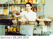Купить «Seller proposes to try pastries», фото № 29241013, снято 22 марта 2017 г. (c) Яков Филимонов / Фотобанк Лори