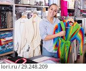 Купить «Smiling girl customer looking through bathrobes», фото № 29248209, снято 21 октября 2018 г. (c) Яков Филимонов / Фотобанк Лори