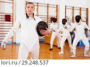Купить «Active young male fencer in uniform standing with mask and foil at fencing room», фото № 29248537, снято 11 июля 2018 г. (c) Яков Филимонов / Фотобанк Лори