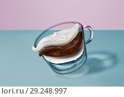 Купить «Separate flying layers of coffee, milk, water, milk foam in the coffee drink in a transparent cup on a duotone background.», фото № 29248997, снято 26 апреля 2018 г. (c) Ярослав Данильченко / Фотобанк Лори
