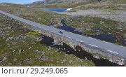 Купить «Мотоцикл едет по высокогорной дороге. Живописная трасса Fv243 Aurlandsfjellet между городами Лердальсёйри (Laedalsoyri) и Эурланнванген (Aurlandsvangen), Норвегия», видеоролик № 29249065, снято 1 октября 2018 г. (c) Кекяляйнен Андрей / Фотобанк Лори